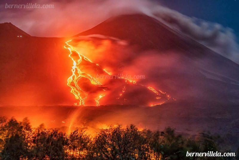 Rayas anaranjadas llameantes que descienden de una montaña oscura bajo el aire humeante.