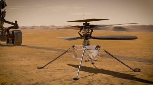 4-legged boxy device with wide rotor blades on brown landscape with part of rover visible.