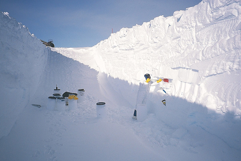 White cylinders with black tops standing in a large snow trench.