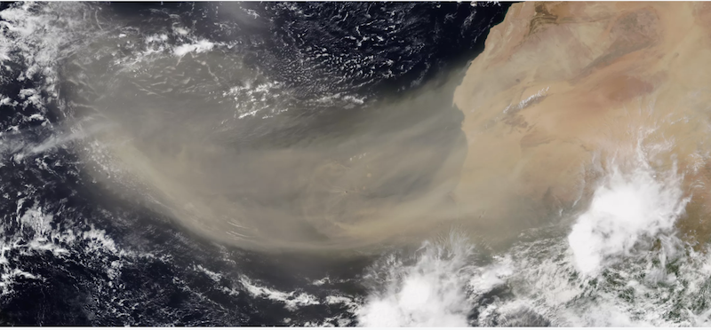 Orbital view of Earth with wide tan streak reaching from Africa out across the cloud-spotted blue Atlantic ocean.