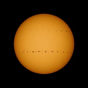 The round disk of the sun, with sunspots crossing it in 2 bands, one in the northern and one in the southern hemisphere.
