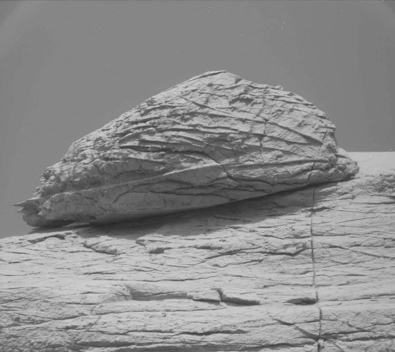 Walnut-shaped rock sitting on larger rocky outcrop.