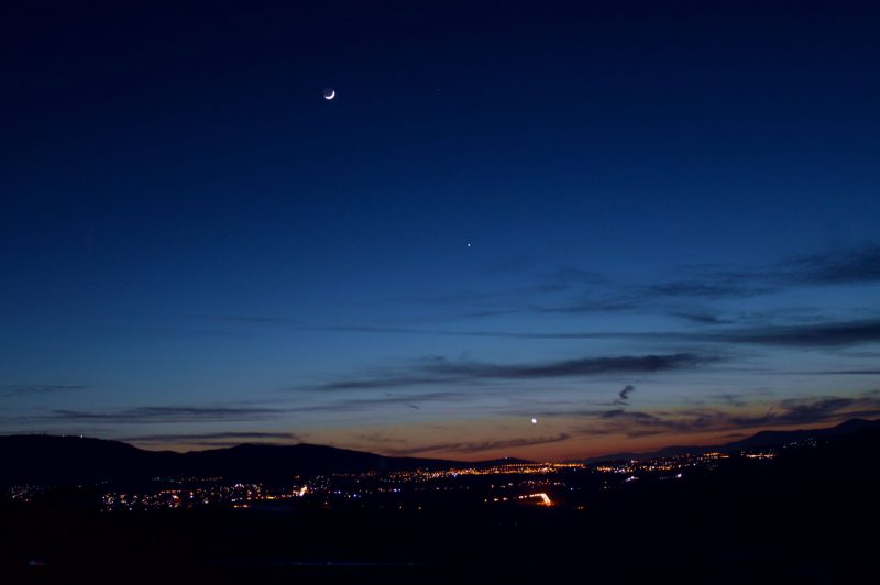 A colorful sunset with a thin crescent moon, overlooking a small city nestled in a valley, together with two bright planets.