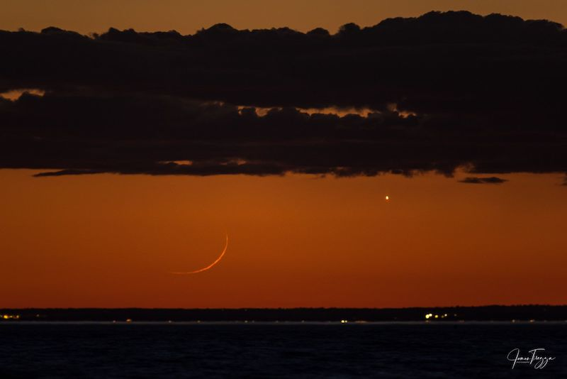 Orange sky with dark stripes at top (due to clouds) and bottom (horizon), with a very thin crescent moon to the left and Venus to the right.