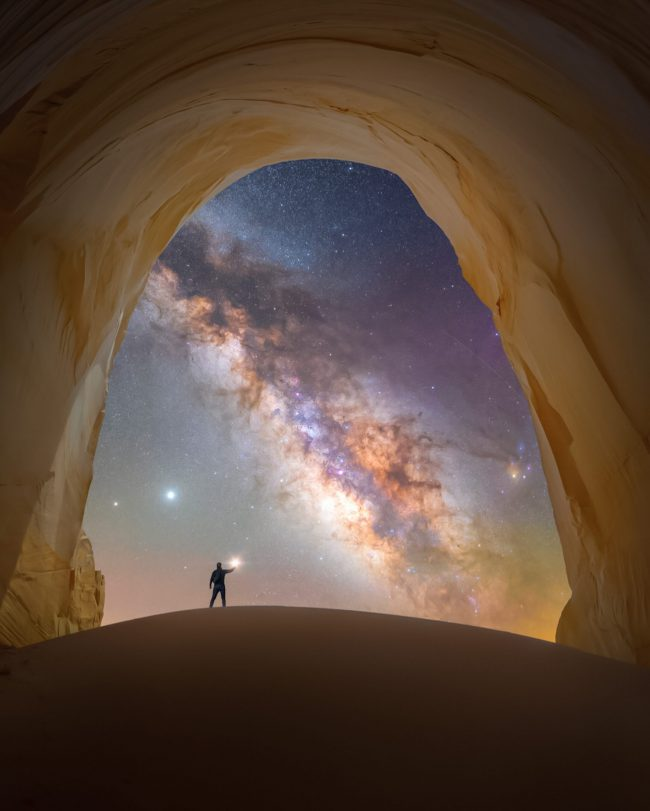 Man standing under rocky arch with Milky Way cutting through sky behind.