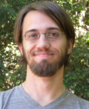 Smiling young man with glasses and beard in front of greenery.