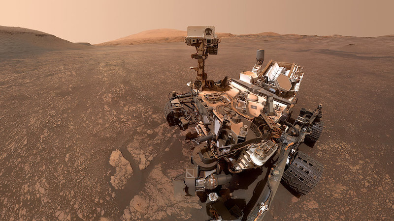 Wheeled robotic rover on brownish rocky terrain with hills in background.
