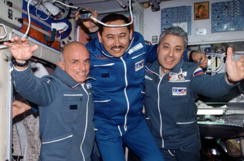 Three men floating in their astronaut uniforms aboard the ISS with technical equipment in the background.