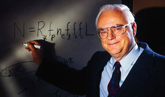 Man with white hair and glasses writes equation on whiteboard.
