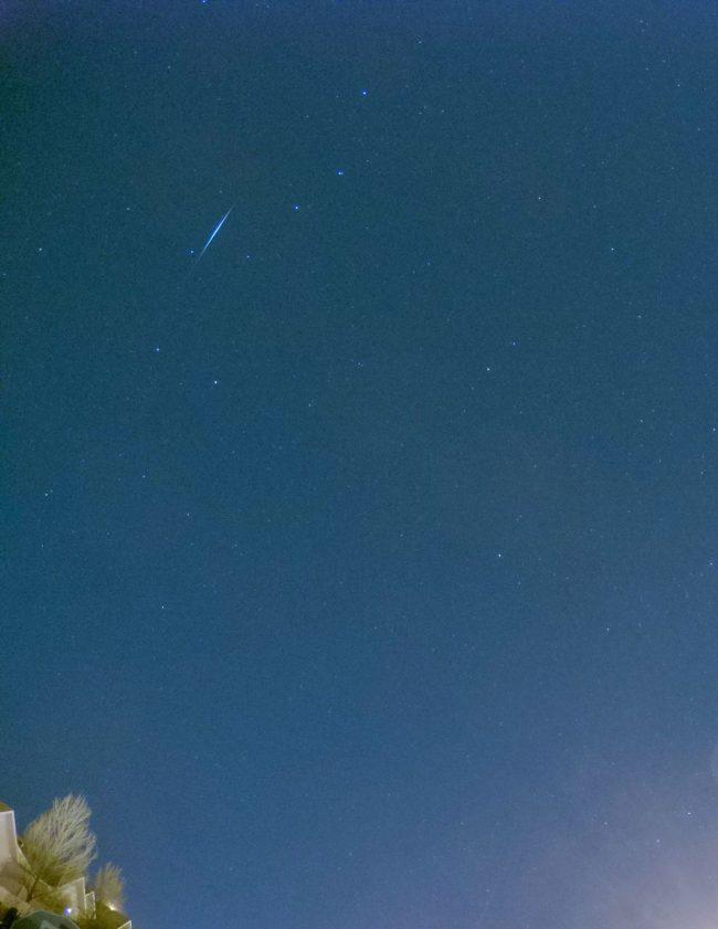 Blue background with short, thin streak of light blue against scattered stars.