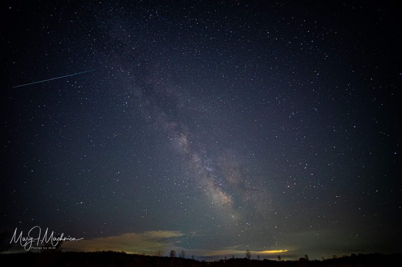 Cloudy stretch of Milky Way across starry sky with long thin streak high above horizon.