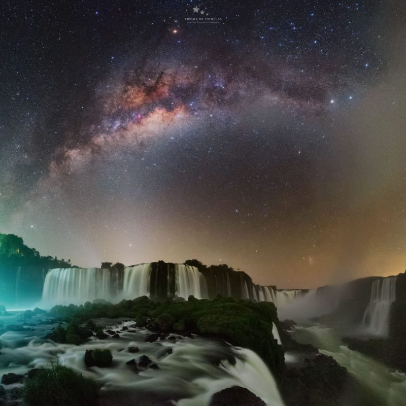 Wide waterfalls in foreground with arching Milky Way behind and other light effects in the sky.