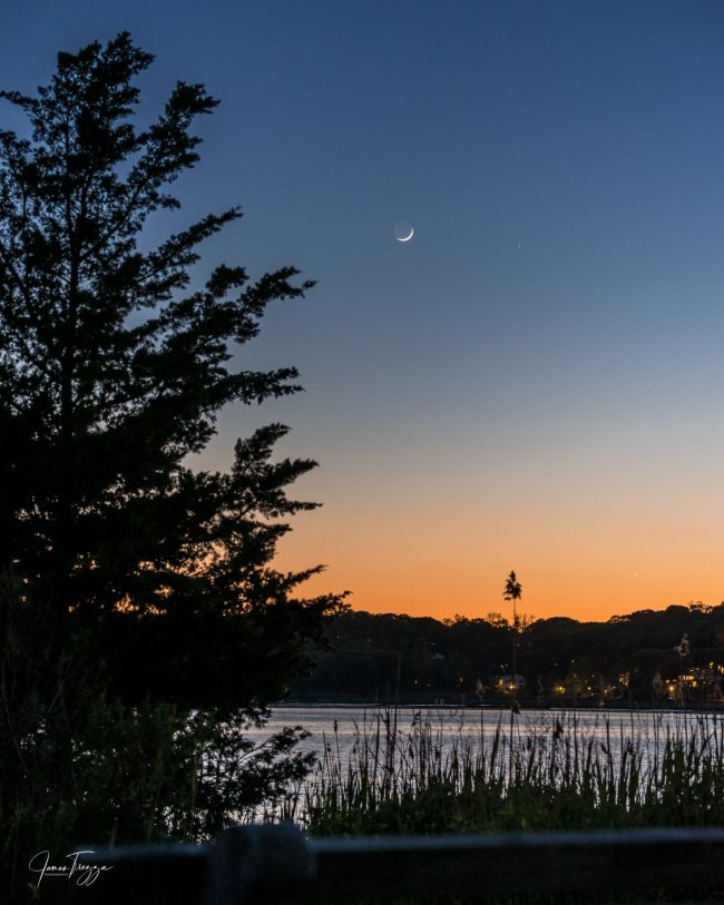 A lake shore at sunset with the moon and two bright planets.