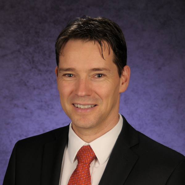 Man with dark hair in suit and red tie.