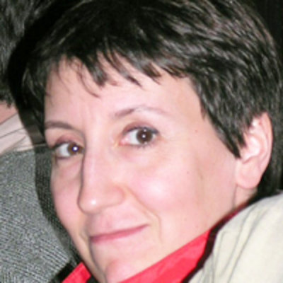 Lightly smiling woman with short hair.