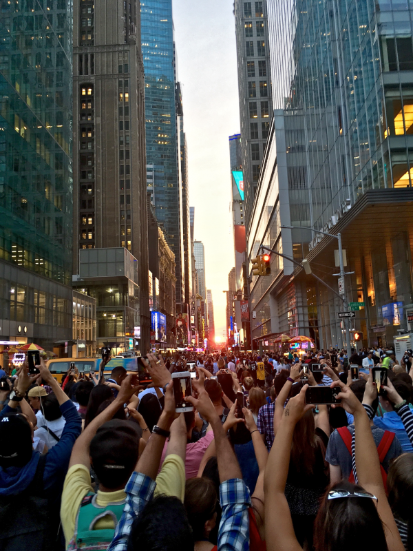 Manhattanhenge sunset and dense crowd of tourists holding cameras up.