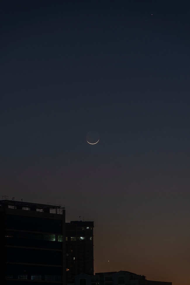 Young crescent moon like a boat, with bright planets Venus at the bottom and Mercury at the top right.