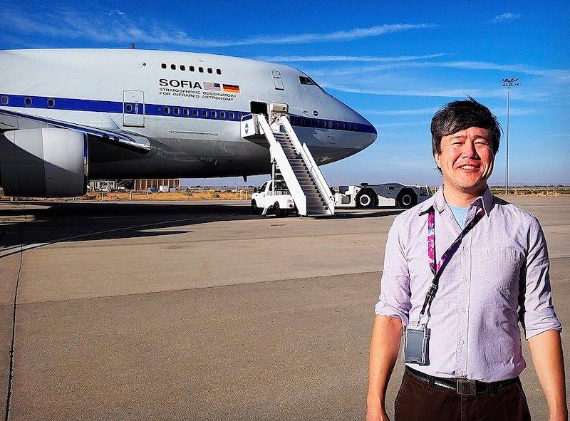 Man standing near jet plane on tarmac.