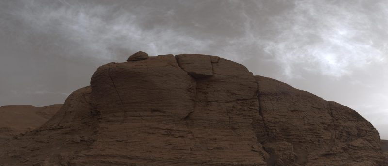 Cloudy sky in shades of gray over rusty dry rock outcropping.