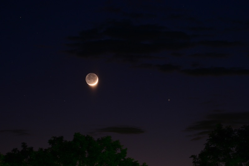 Dark sky with a crescent moon lit up by Earth-shine, Mercury to the right.