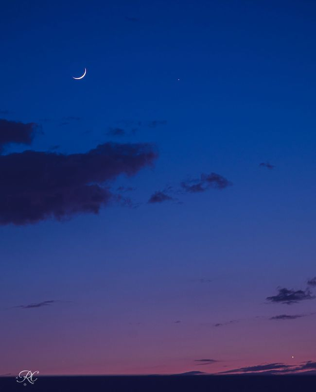 Purple to dark blue sky, with some clouds, a crescent moon at top left and bright dots of Mercury and Venus.