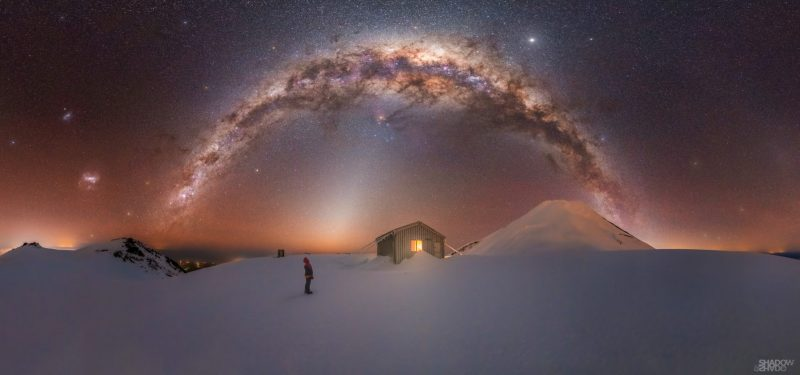Distant person standing in snow looking up at arching Milky Way.