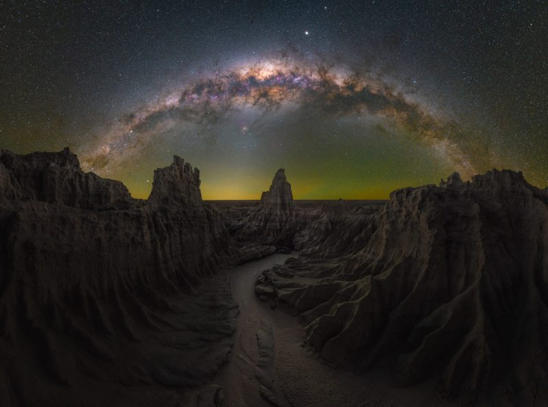 Milky Way arching over rocky landscape and river.