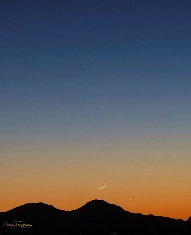 A colorful sunset with a thin crescent moon, right over a mountainous silhouette, together with two bright planets.