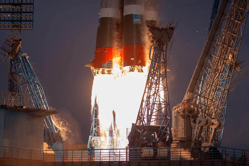 Bright white flames appear out the bottom of a rocket lifting off into the sky.