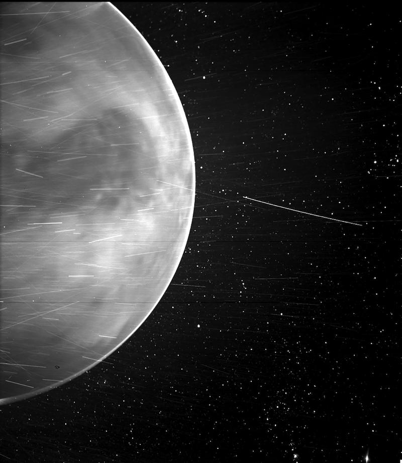 Черно-белая планета с множеством тонких линий вокруг нее и звездами на заднем плане.