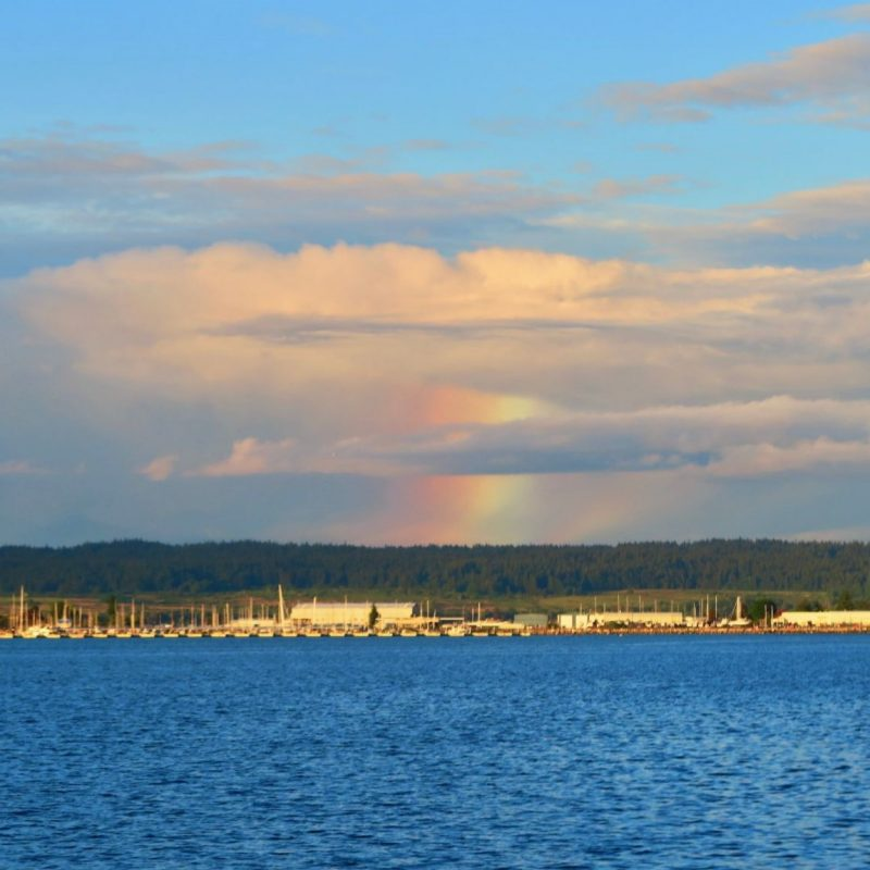 Rainbow patch coming out of bottom of cloud like a rain shaft.