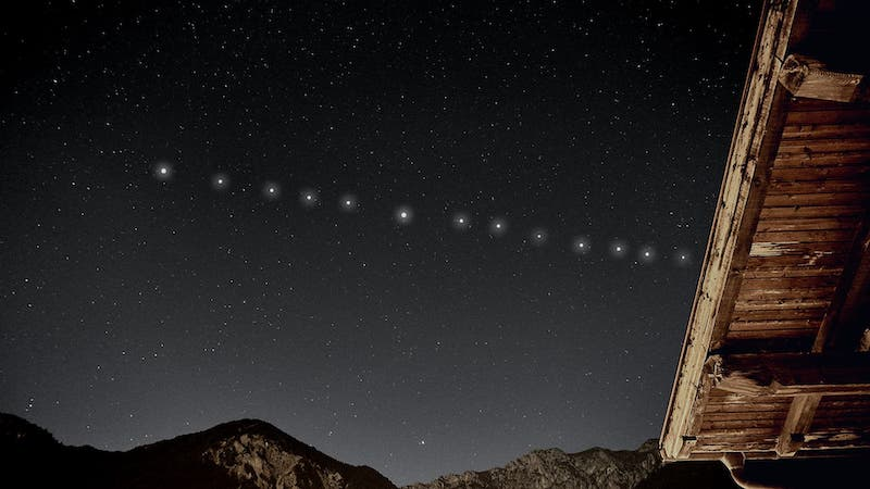 A line of 13 evently spaced white dots across a starry sky above mountains.