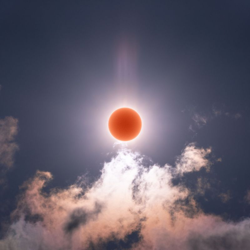 The sun imaged as a red orb in the center with rays emanating from it and lit up clouds below.