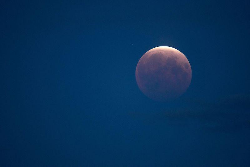 Lunar eclipse: bright orange and white moon on a dark blue sky background.