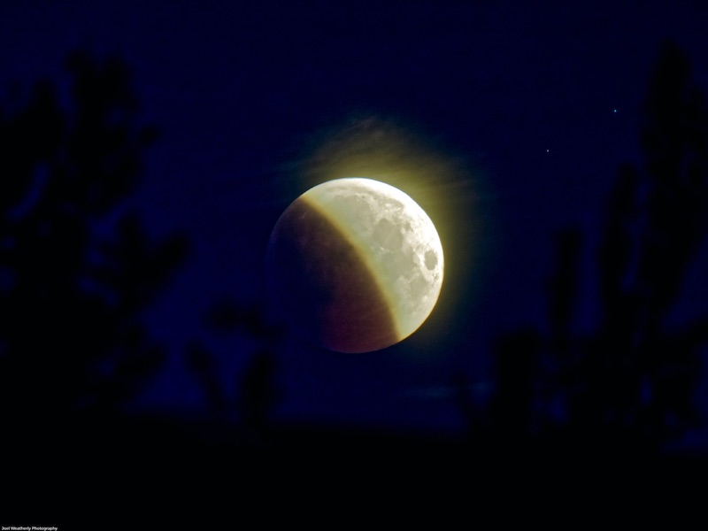 Lunar eclipse: bright yellow half moon, with visible features, against a black sky background.