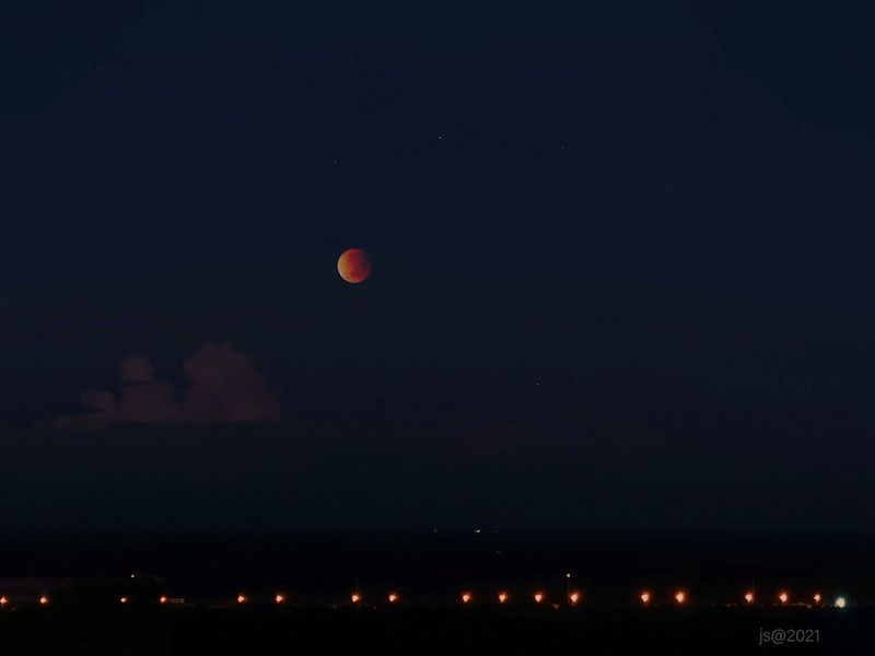 Lunar eclipse: bright orange and white moon on a black sky background.