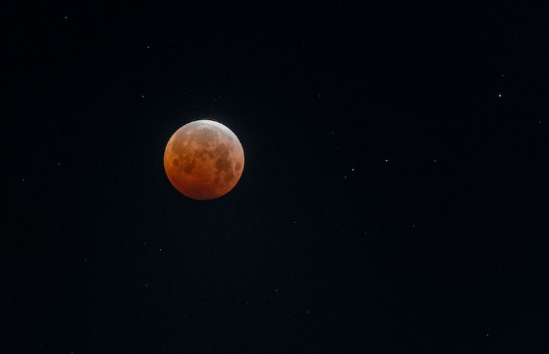 Lunar eclipse: shining orange and white moon on a black sky background with scattered stars.