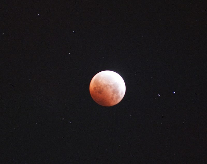 Lunar eclipse: Bright orange and white ball on a black background.