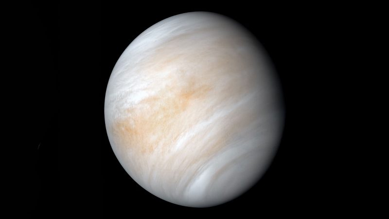 Nearly full view of Venus covered in white and salmon clouds.