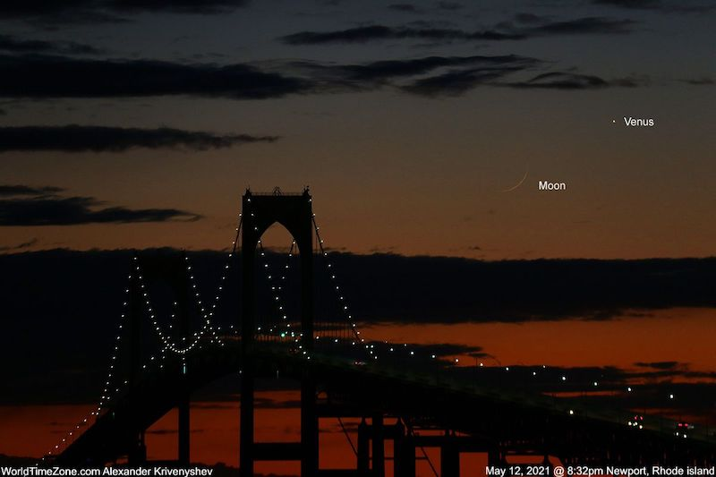 Bridge in silhouette in the foreground during dusk, very young moon and Venus visible on orange sky.