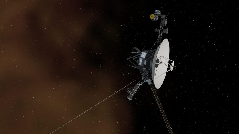 Small, boxy spacecraft with a big dish antenna on part deep orange, part black background.