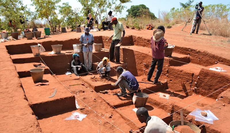People working in a shallow excavation site.