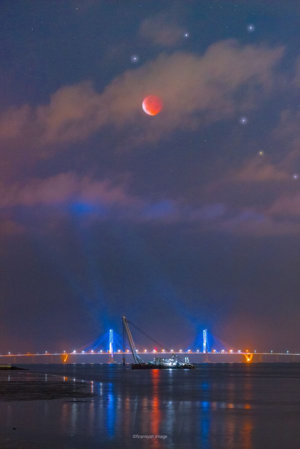 Orange moon above a lighted bridge, with scattered bright stars visible.
