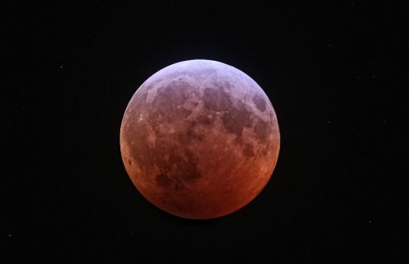 Lunar craters and 'seas' on the reddish moon's surface, visible during the eclipse.