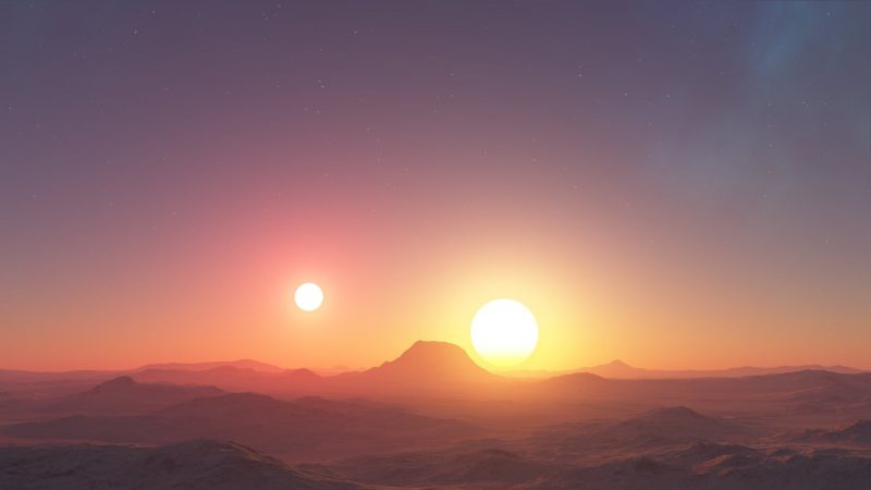 Two suns rising over a barren landscape with mountains in the distance.