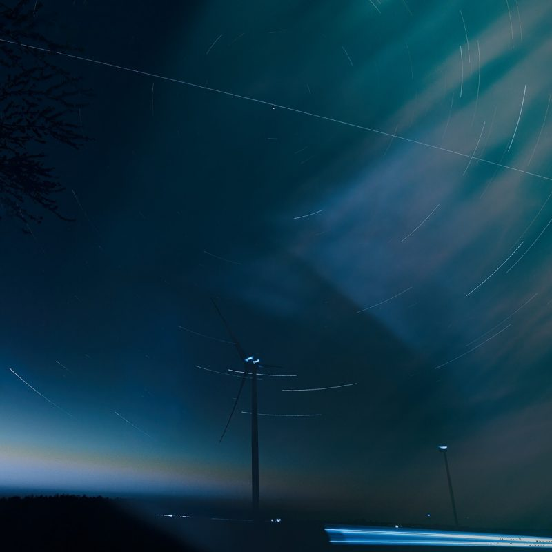 A blue background with a white line crossing the sky, near a medium-bright star and a few curved star trails.