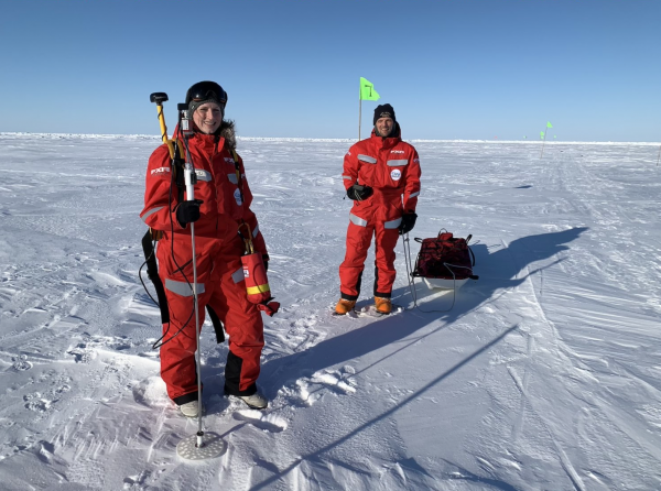 Two people in bright orange jumpsuit, standing on a field of Arctic sea ice.