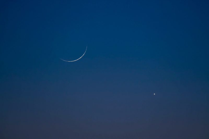 Very young and thin crescent moon, with bright planet Venus, in a twilight sky.