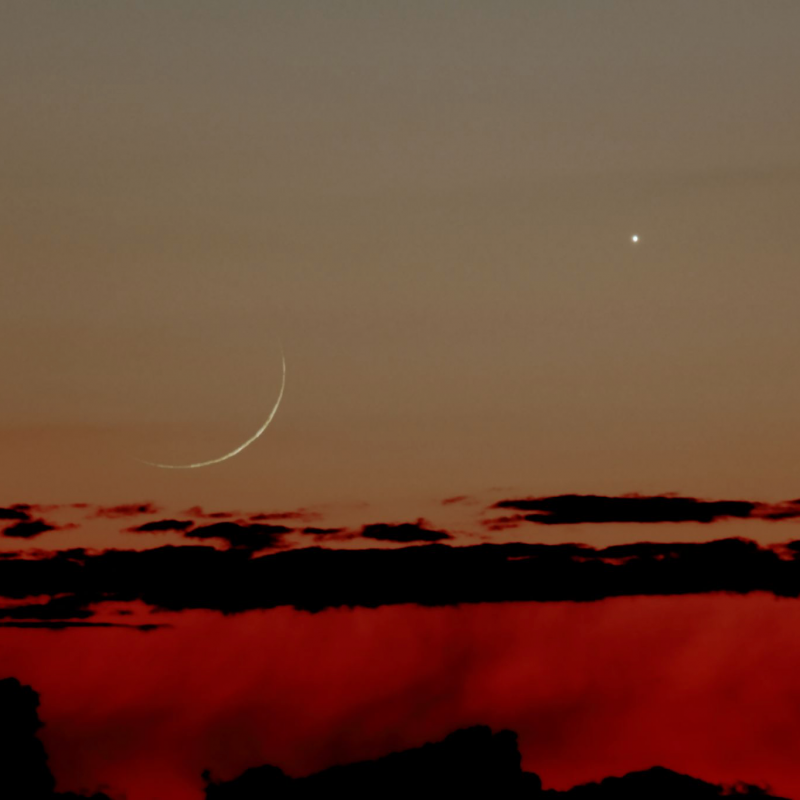 Threadlike crescent moon and bright Venus above linear clouds, in sky fading from red to dark orange.