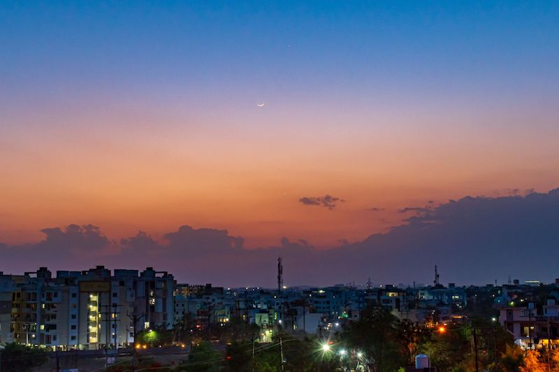 Colorful evening sky with a faint young moon, Mercury and Venus and cityscape in foreground.